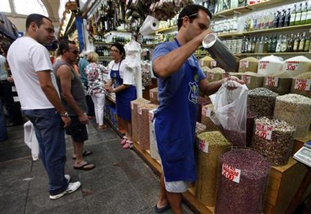 A vendor fills a bag of beans next to customers at the Municipal Market in Sao Paulo February 4, 2012. REUTERS/Nacho Doce