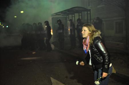 A protester holding flowers is pictured during a demonstration in Maribor December 3, 2012. REUTERS/Srdjan Zivulovic