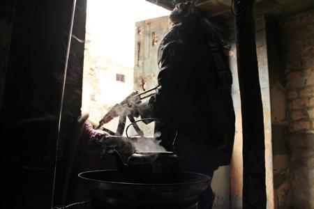 A Free Syrian Army fighter takes his position next to a teapot in Qastal Harami area in Aleppo in this picture released December 19, 2012. Picture released December 19, 2012. REUTERS/Saad Al-Jabri