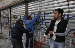 A police officer conducts a body search on an immigrant during an operation in the centre of Athens December 5, 2012. REUTERS/John Kolesidis