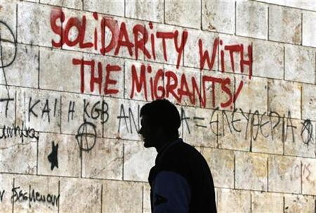 A man walks past graffiti outside the Athens' Academy in central Athens December 6, 2012. REUTERS/Yannis Behrakis