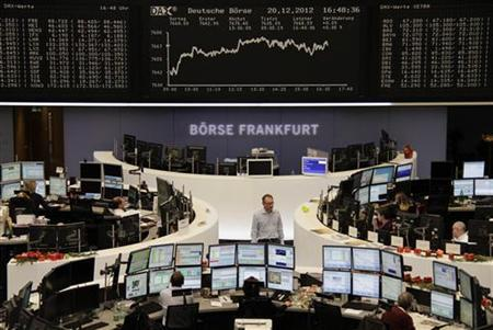 Traders are pictured at their desks in front of the DAX board at the Frankfurt stock exchange December 20, 2012. REUTERS/Remote/Janine Eggert (GERMANY - Tags: BUSINESS)