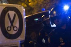 El Congreso de los Diputados español dio luz verde el jueves a los Presupuestos Generales del Estado (PGE) más austeros de la democracia después del debate de las enmiendas incorporadas a la ley en su tramitación en el Senado. En la imagen, varios policías junto a un cartel contra los recortes en Madrid el 19 de diciembre de 2012. REUTERS/Juan Medina