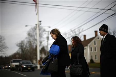 A woman cries while leaving the funeral of six-year-old Benjamin Wheeler who was killed December 14 in a deadly shooting at Sandy Hook Elementary school in Newtown, Connecticut, December 20, 2012. REUTERS/Eric Thayer