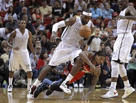 Miami Heat's LeBron James (center L) collides with Washington Wizards' Cartier Martin (center R) in the second half of their NBA basketball game in Miami, Florida December 15, 2012. REUTERS/Andrew Innerarity