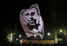 An opposition activist waves a flag portraying journalist Al-Hosseiny Abu Deif during his funeral in Cairo December 19, 2012. Abu Deif died on December 6, 2012 during clashes between supporters and rivals of Egyptian President Mohamed Mursi. Egyptian Islamist groups are planning a mass protest in Alexandria on Friday, a move that will raise tensions a day before the final stage of a referendum on a new constitution that has split the nation. REUTERS/Khaled Abdullah
