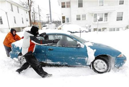 Michael Tweedt (C) directs Hailey Pettit (in car) as Kimberlee Taylor helps push the car free from the snow Cedar Falls, Iowa, December 20, 2012. The first major winter storm of the year took aim at the U.S. Midwest on Thursday, triggering high wind and blizzard warnings across a widespread area, and a threat of tornadoes in Gulf Coast states to the south. REUTERS/Matthew Putney/The Waterloo Courier/Handout
