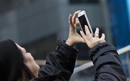 A woman takes a picture with her phone in Times Square in New York, December 18, 2012. REUTERS/Andrew Burton