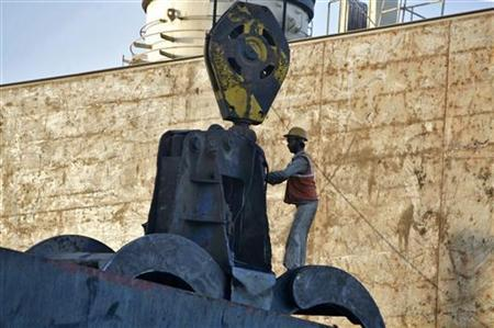 A man works on the crane of a cargo ship at Mundra port in Gujarat September 24, 2012. REUTERS/Amit Dave/Files