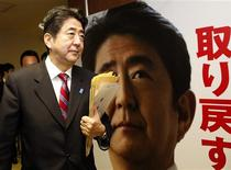 Shinzo Abe, Japan's incoming prime minister and the leader of Liberal Democratic Party (LDP), walks past his portrait after attending a meeting at the LDP headquarters in Tokyo December 21, 2012. REUTERS/Toru Hanai