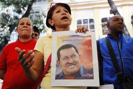 A supporter of Venezuelan President Hugo Chavez holds a picture of him, as she attends a ceremony to pray for his health in Caracas December 20, 2012. REUTERS/Carlos Garcia Rawlins