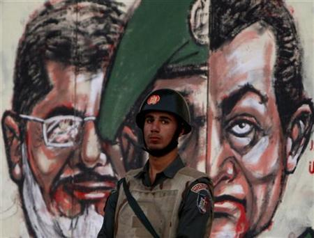 A member of Egypt's Republican Guard stands in front of a wall of the presidental palace bearing caricatures of Egypt's current President Mohamed Mursi (L) and former president Hosni Mubarak (R) in Cairo December 18, 2012. REUTERS/Mohamed Abd El Ghany