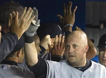 New York Yankees Casey McGehee (R) is congratulated in the dugout after he hit a three run home run against the Toronto Blue Jays in the fourth inning of their American League MLB baseball game in Toronto August 11, 2012. REUTERS/Fred Thornhill