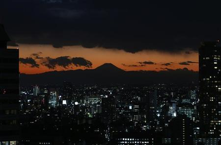 The silhouette of Japan's highest mountain Mount Fuji (C) is seen beyond buildings in Tokyo December 12, 2012. REUTERS/Issei Kato