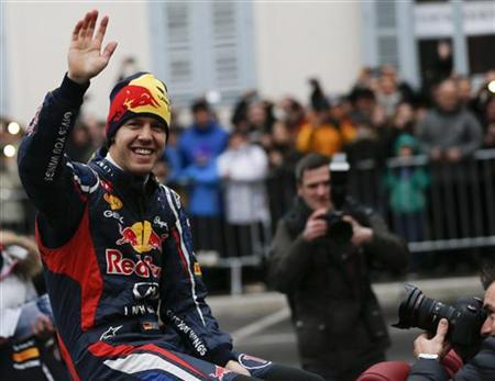 Red Bull three-time Formula One world champion Sebastian Vettel of Germany waves to fans as he sits in a convertible during a promotional event in the Austrian city of Graz December 1, 2012. REUTERS/Leonhard Foeger