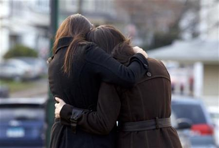 Two women embrace outside the wake for Victoria Soto in Stratford, Connecticut, December 18, 2012. Soto, a teacher, was a victim of Friday's shooting at Sandy Hook elementary School in Newtown, Connecticut. REUTERS/Michelle McLoughlin