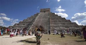Pessoas com roupas de guerreiros astecas dançam diante da pirâmide Kukulkan, em Chichen Itza, no México. Milhares de místicos, hippies e pessoas com inquietações espirituais devem comparecer às ruínas das cidades maias para celebrar um novo ciclo do calendário maia, ignorando os temores de quem acha que o mundo vá acabar por causa disso. 20/12/2012 REUTERS/Victor Ruiz Garcia