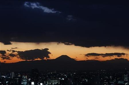 The silhouette of Japan's highest mountain Mount Fuji is seen beyond buildings in Tokyo December 12, 2012. REUTERS/Issei Kato