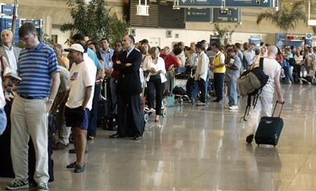 Travelers form a long line while waiting to go through customs at the International Airport of Galeao, in Rio de Janeiro, March, 11, 2004. REUTERS/Bruno Domingos