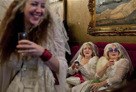 Participants, dressed in bridal outfits, drink champagne during the March of Brides parade through downtown San Francisco March 18, 2012. REUTERS/Jana Asenbrennerova/Files