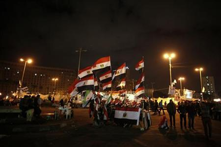 People walk past a stall displaying Egyptian flags for sale at Tahrir Square where protesters opposing President Mohamed Mursi are camping in Cairo December 19, 2012. REUTERS/Khaled Abdullah