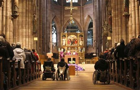 Handicapped people in wheelchairs attend a catholic mass to commemorate the victims of a fire in a workshop for disabled people, at Muenster church in Freiburg November 28, 2012. REUTERS/Lisi Niesner