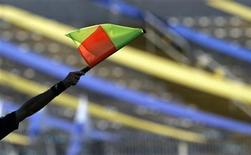 """Боковой судья поднимает флаг, чтобы зафиксировать офсайд в финальном матче мальтийской Премьер-Лиги между """"Марсашлокком"""" и """"Слимой Уондерерс"""" 13 мая 2007 года. REUTERS/Darrin Zammit Lupi"""
