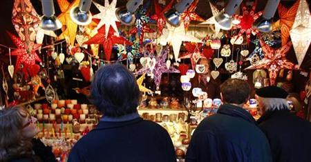 People visit a shop selling illuminated window stars in different colours at Munich's Christmas market December 18, 2012. REUTERS/Michaela Rehle