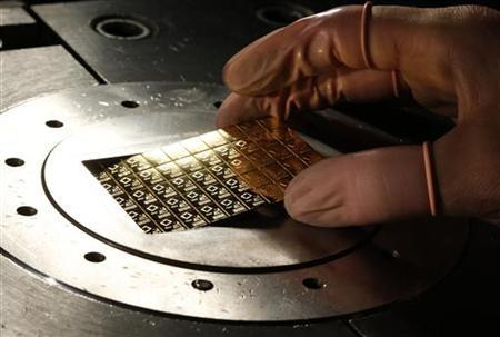 An employee takes a gold Combibar out of a press machine at a plant of gold refiner and bar manufacturer Valcambi SA in the southern Swiss town of Balerna December 20, 2012. REUTERS/Michael Buholzer