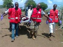 Members of the Kenya Red Cross carry an injured man after an attack in his village at Tana River district in Kenya's coastal Tana Delta region December 21, 2012. Thirty-nine people, including several children, were killed in tribal violence in the Tana Delta region on Friday, police said, heightening security concerns ahead of next year's presidential election. REUTERS/Kenya Red Cross/Handout