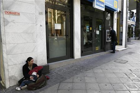 A woman begs as she sits outside a Hellenic Postbank branch in Athens December 7, 2012. REUTERS/Yorgos Karahalis