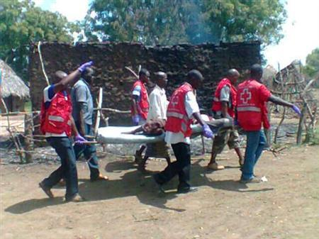 Members of the Kenya Red Cross carry an injured man after an attack in his village at Tana River district in Kenya's coastal Tana Delta region December 21, 2012. REUTERS/Kenya Red Cross/Handout