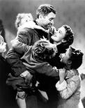 """NBC television network will air director Frank Capra's classic movie """"It's A Wonderful Life"""" starring Jimmy Stewart (C), shown with the film's cast in an undated publicity photo, on December 25, 2000 (8-11p.m. ET). REUTERS/Handout Old"""