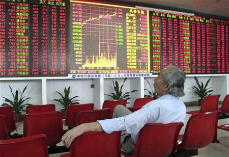 An investor looks at an electronic board showing stock information at a brokerage house in Haikou, China's Hainan province December 14, 2012. REUTERS/China Daily