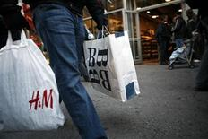 A shopper carrying shopping bags walks past retail stores in New York's Times Square November 23, 2007. REUTERS/Brendan McDermid