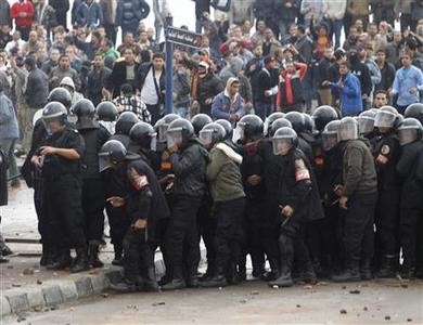 Riot policemen look as they stand between protesters opposing Egyptian President Mohamed Mursi and others supporting him (not pictured) in Alexandria December 21, 2012. Supporters of President Mohamed Mursi and his opponents hurled rocks at each other in Egypt's second city on the eve of a final vote on a new constitution shaped by Islamists. REUTERS/Khaled Abdullah