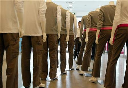 A Chinese shopper looks at a row of mannequins in trousers and shirts at a clothes store in Shanghai September 4, 2005. REUTERS/Aly Song CC/TZ/Files