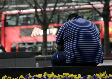 A man sits on a wall in the Canary Wharf financial district of London, April 1, 2009. REUTERS/Simon Newman