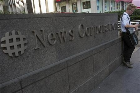 A passer-by stands in front of the News Corporation building in New York June 28, 2012. REUTERS/Keith Bedford/Files