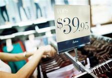 La costumbre de algunos clientes de probarse una prenda y luego comprarla más barata en Amazon.com u otras páginas web, conocida como 'showrooming' en inglés, ha llevado a los comerciantes hasta el punto de esconder los códigos de barras, mejorar sus propias páginas web y dar con métodos para que la gente complete su compra en la tienda. En esta imagen de archivo, una dependienta coloca ropa en perchas en una tienda Katies de Specialty Fashion Group, en Sídney, el 11 de diciembre de 2012. REUTERS/Tim Wimborne