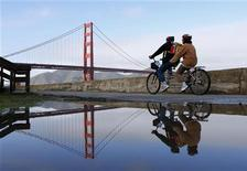 The Golden Gate Bridge is reflected onto a puddle from the early morning rain in San Francisco, California, November 28, 2012. REUTERS/Beck Diefenbach
