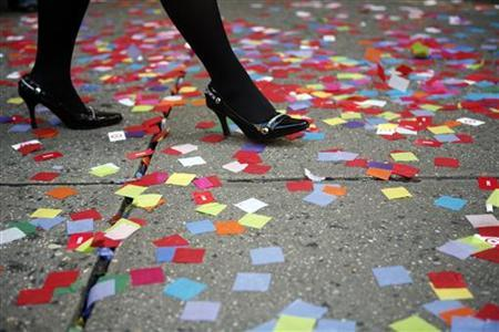 A woman walks on a confetti-strewn sidewalk during a rehearsal for New Year's Eve celebrations at Times Square in New York December 29, 2006. REUTERS/Eric Thayer