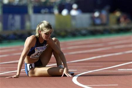 Suzy Favor-Hamilton of the U.S. sits on the track after a DNF in her heat of the 1500 meter semifinal at the World Championships in Athletics, in Edmonton August 5, 2001. REUTERS/Gary Hershorn/Files