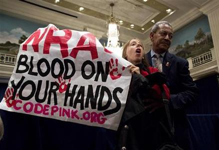 A protestor, holding up a sign, is removed by a security guard during a speech by Wayne LaPierre (unseen), executive vice president of the National Rifle Association (NRA), during a news conference in Washington December 21, 2012. REUTERS/Joshua Roberts
