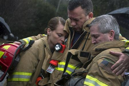 Sandy Hook Village firefighters observe a moment of silence near Sandy Hook Elementary in Newtown, Connecticut December 21, 2012. Many Americans remembered the victims of the Newtown, Connecticut, school massacre with a moment of silence on Friday, as a powerful U.S. gun rights lobbying group prepared to plunge into the national debate over gun control. REUTERS/Adrees Latif