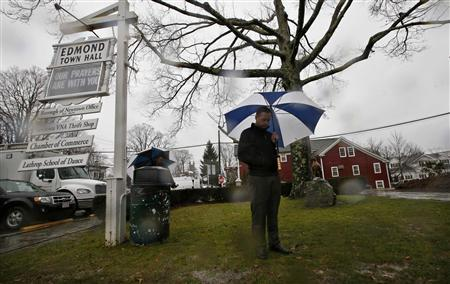 A man stands beneath an umbrella in a driving rain outside the Edmond Town Hall during a moment of silence and ringing of church bells at 9:30am EDT for the victims of the December 14 shooting at the Sandy Hook Elementary school in Newtown, Connecticut, December 21, 2012. REUTERS/Mike Segar