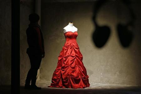 A visitor looks at a wedding dress displayed at the Museum of Broken Relationships installed at the CentQuatre exhibition hall in Paris December 18, 2012. This short-lived exhibition space, in association with the museum with the same name in Zagreb, will run from December 19 to January 20, 2013 and will show relics of sentimental disappointment. REUTERS/Benoit Tessier