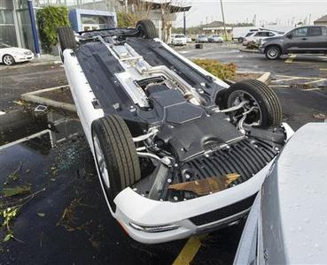 An automobile sits upside down in the car lot of Mercedes-Benz of Mobile following a winter storm in Mobile, Alabama, December 20, 2012. The first major winter storm of the year took aim at the U.S. Midwest on Thursday, triggering high wind and blizzard warnings across a widespread area, and a threat of tornadoes in Gulf Coast states to the south. REUTERS/Jon Hauge