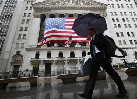 Morning commuters walk pass the New York Stock Exchange in the rain, June 4, 2012. REUTERS/Brendan McDermid