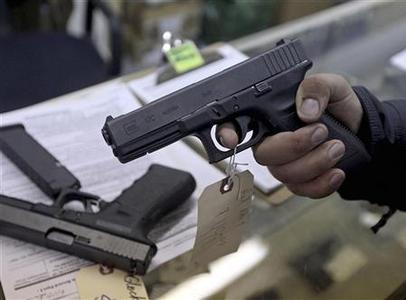 A customer looks over a Glock 17 9mm hand gun at the Guns-R-Us gun shop in Phoenix, Arizona, December 20, 2012. REUTERS/Ralph D. Freso